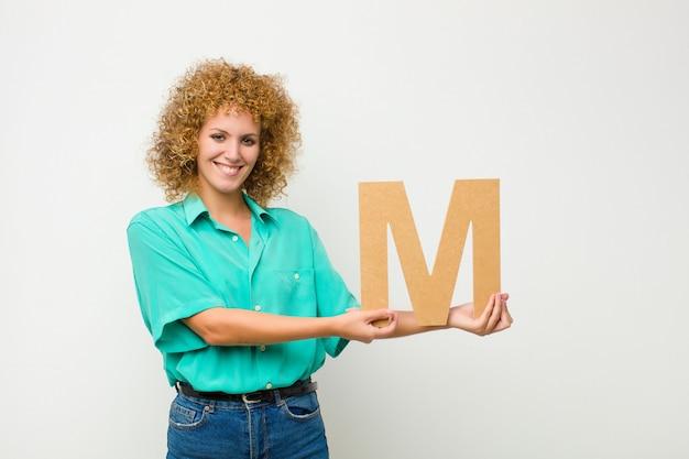 Возбужденный, счастливый, радостный, держа букву м в алфавите, чтобы сформировать слово или предложение.