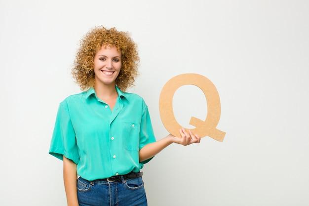 Возбужденный, счастливый, радостный, держа букву q в алфавите, чтобы сформировать слово или предложение.
