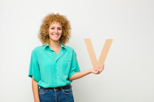 Возбужденный, счастливый, радостный, держа букву v в алфавите, чтобы сформировать слово или предложение.