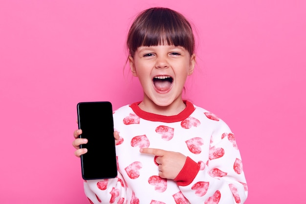 Excited happy laughing female kind with opened mouth holding cell phone in hands and pointing at blank display with index finger, posing isolated over pink wall.