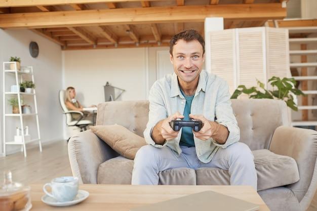 ジョイスティックでソファに座って、リビングルームでコンピュータゲームで遊んで興奮した幸せな男