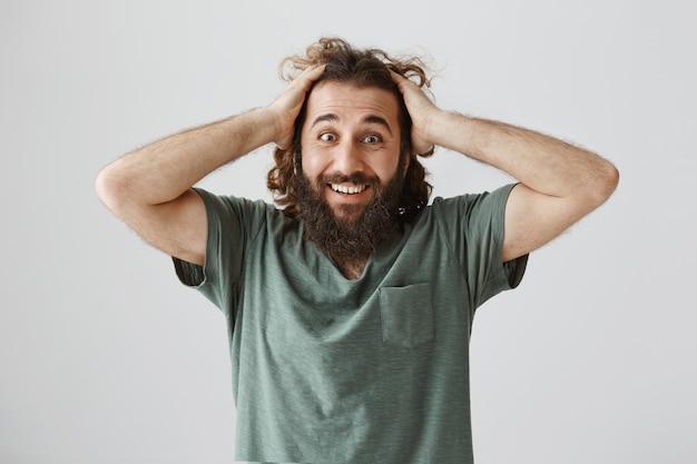 驚いて笑って興奮している幸せな男、素晴らしいニュースを受け取る