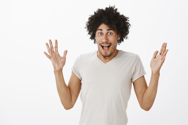 素晴らしいニュースを語り、手を上げ、何か大きなことを発表する興奮した幸せな男