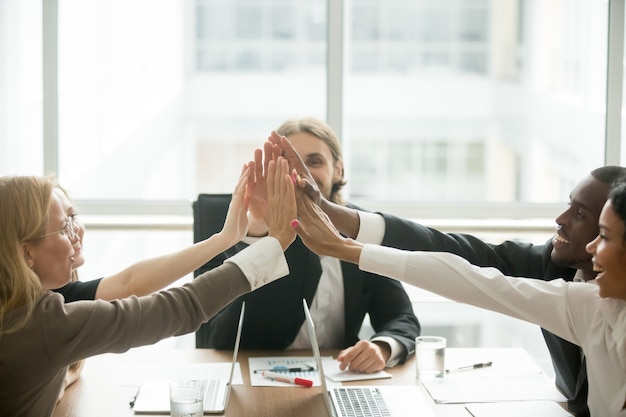 Excited happy multiracial business team giving high-five at office meeting