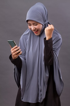 Excited, happy muslim woman using smartphone, wireless internet device