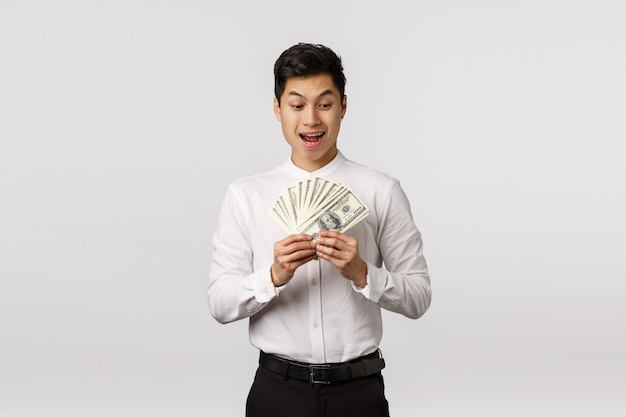 Excited and happy, pleased handsome asian businessman made good deal, counting money and smiling thrilled, winning bid, got big cash and celebrating, ready to treat himself,