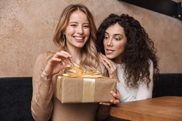 Возбужденные счастливые красивые девушки друзья сидят в кафе с подарочной коробкой