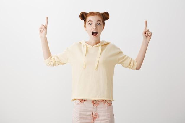손가락을 가리키는 흥분된 행복 빨강 머리 소녀