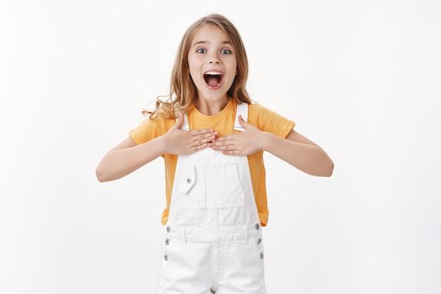 ブロンドの髪の青い目をした興奮した幸せなスマートな小さな子供、胸を誇らしげに叩き、個人的な成果について笑顔で話し、自慢し、彼女がそれを行うことができると誓う、ボランティア、白い壁に立つ