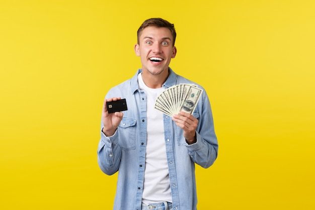 Excited happy smiling blond man looking thrilled and showing money with credit card, ready to pay in cash for product, paying for something with joyful expression, yellow background.
