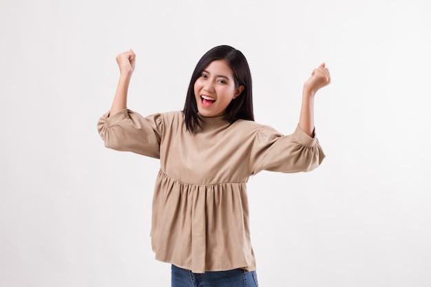 Взволнованная счастливая улыбающаяся умная повседневная азиатская женщина позирует в веселой, успешной позе
