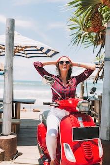 Eccitata ragazza alla moda felice indossa occhiali da sole neri e berretto rosso, camicia a quadri si diverte sulla bici rossa sull'oceano e foglie di palma, vacanze estive, viaggi, isola