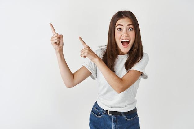 Eccitata felice e sorpresa bella giovane donna rivolgi la tua attenzione al banner, puntando le dita a sinistra e urlando gioiosa, stai in piedi sul muro bianco