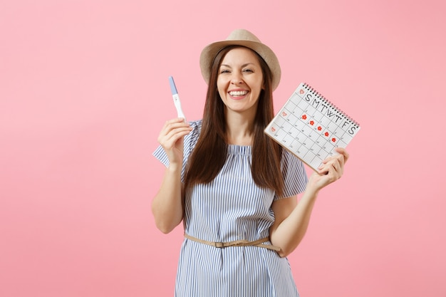 Excited happy woman in blue dress, hat hold in hand pregnancy test, periods calendar for checking menstruation days isolated on pink background. medical, healthcare, gynecological concept. copy space.