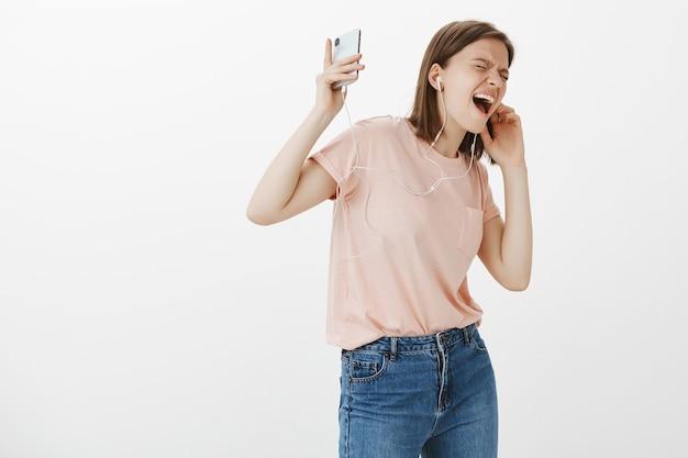 Donna felice eccitata che gode della musica fantastica in cuffie, balla e canta con il telefono cellulare