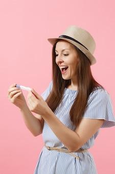 파란 드레스를 입은 흥분한 행복한 여성, 모자를 손에 들고 분홍색 배경에 격리된 임신 테스트를 보고 있습니다. 의료 의료 부인과, 임신 다산 출산 사람들 개념. 공간을 복사합니다.