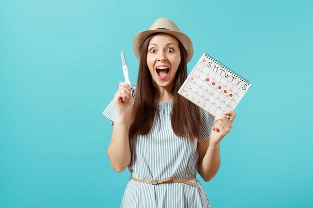 파란 드레스를 입은 흥분한 행복한 여성, 모자를 손에 들고 임신 테스트, 파란색 배경에 격리된 월경일을 확인하기 위한 기간 달력. 의료, 건강 관리, 부인과 개념입니다. 공간을 복사합니다.