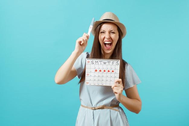 青いドレス、帽子を手に妊娠検査、青い背景で隔離の月経日をチェックするための期間カレンダーで興奮した幸せな女性。医療、ヘルスケア、婦人科の概念。スペースをコピーします。
