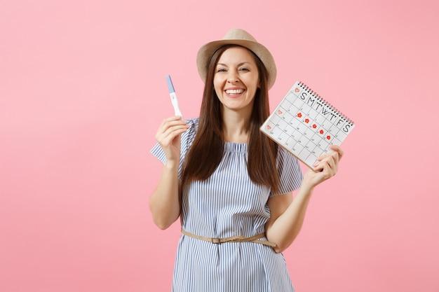파란 드레스를 입은 흥분된 행복한 여성, 모자를 손에 들고 있는 임신 테스트, 분홍색 배경에 격리된 월경일을 확인하기 위한 기간 달력. 의료, 건강 관리, 부인과 개념입니다. 공간을 복사합니다.