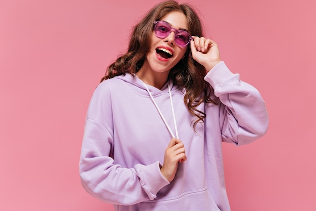 紫色のパーカーで興奮した幸せな女性は広く笑顔