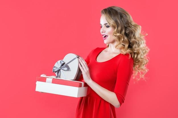 선물을 들고 빨간 드레스에 흥분된 행복 한 여자