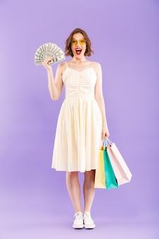 쇼핑백과 돈을 들고 고립 된 행복 한 여자를 흥분.