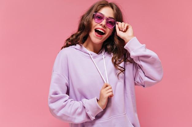 Eccitata donna felice in felpa con cappuccio viola sorride ampiamente