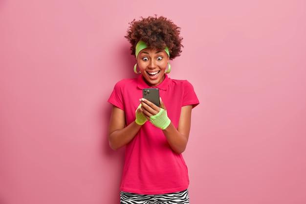 興奮した幸せな女性がスマートフォンのディスプレイで大きな幸せを見つめます