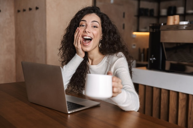 Excited happy woman using laptop computer while sutting at the cafe table and drinking coffee