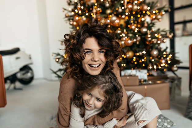 Excited happy woman with little daughter laughing and having fun while celebrating christmas