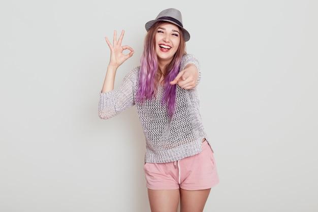 Donna felice eccitata con capelli viola che punta alla telecamera con il dito e che mostra segno giusto. gesto di approvazione, che esprime emozioni positive, isolato sopra il muro bianco.