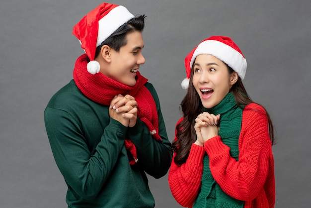 Excited happy young asian couple wearing colorful christmas theme attire