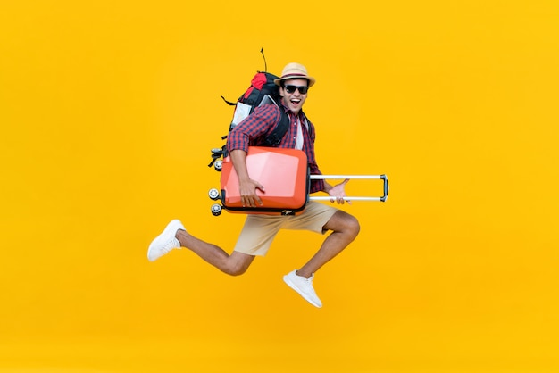 Excited happy young asian man tourist with luggage jumping