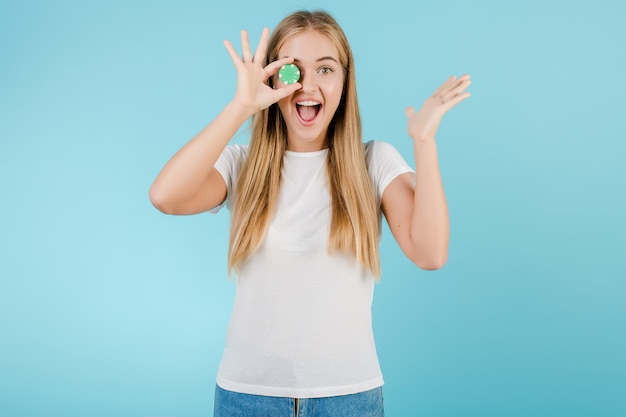 Excited happy young blonde woman with poker chip covering her eye isolated over blue