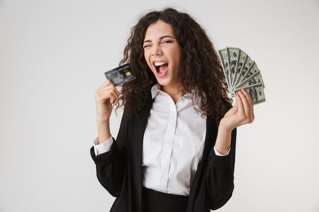 Возбужденная счастливая молодая бизнес-леди с кредитной картой и деньгами.