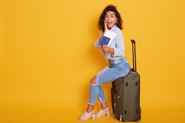 Excited and happy young cheerful female tourist sitting on her large suitcase
