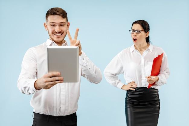 喜んでカメラを見て興奮した幸せな若いカップル。ビジネスマンと青いスタジオの背景に分離された女性