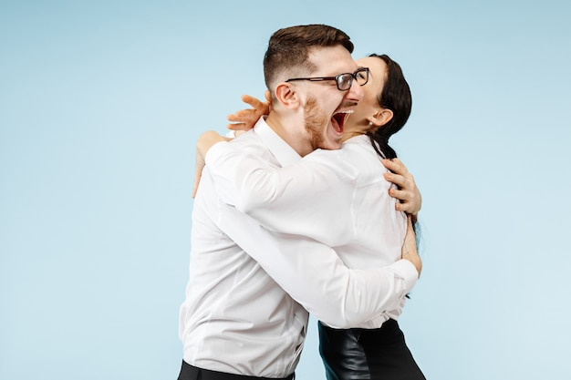 Excited happy young couple looking at camera with delight. businessman and woman isolated on blue studio background