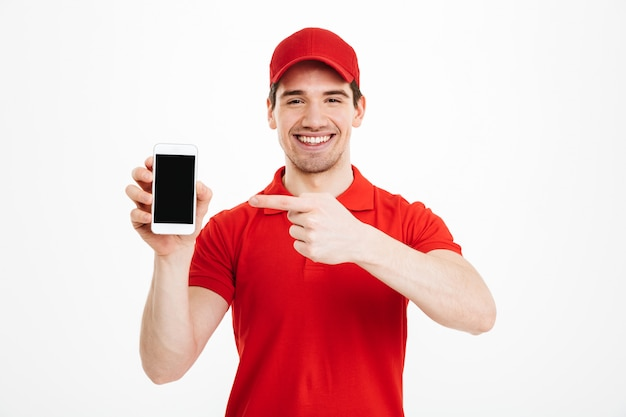 Excited happy young delivery man showing display of mobile phone.