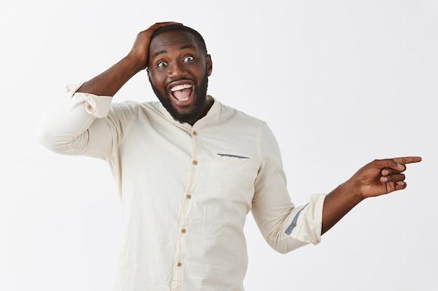 Ragazzo giovane felice emozionante che posa contro il muro bianco