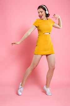 Excited happy young lady in yellow dress dancing
