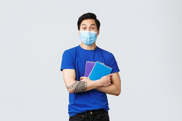 Excited счастливый молодой мужской азиатский студент в кампусе медицинской маски возглавляя, усмехаясь и держа тетради