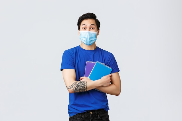 Excited happy young male asian student in medical mask heading campus, smiling and holding notebooks