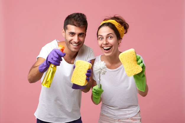 Excited happy young male and female wearing rubber gloves, holding cleaning supplies while tidying up in their apartment
