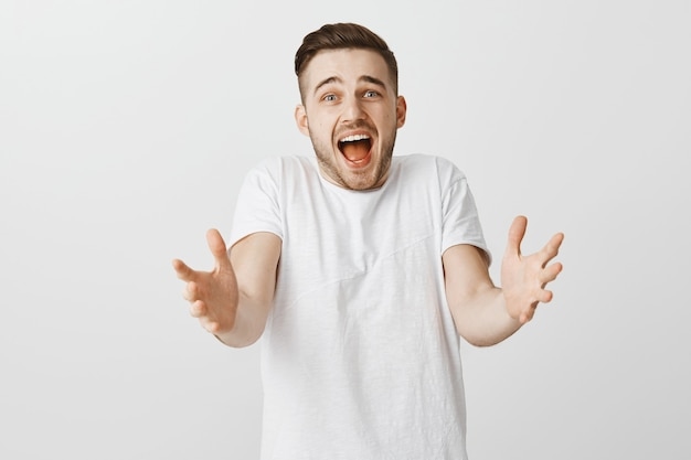 Excited happy young man reaching hands forward to take something