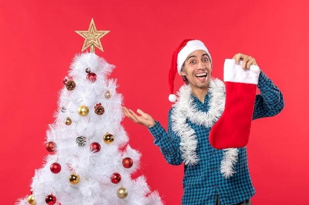 파란색 벗겨진 셔츠에 산타 클로스 모자와 크리스마스 트리 근처 크리스마스 양말을 들고 흥분된 행복 한 젊은 남자