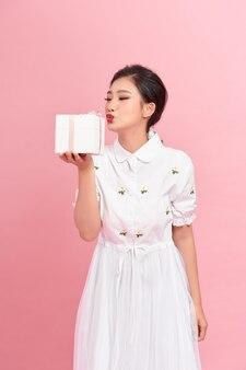 Возбужденная счастливая молодая красивая женщина позирует изолированной на розовом фоне стены, держащей настоящие коробки.