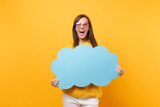 Excited happy young woman in heart eyeglasses holding empty blank blue say cloud, speech bubble isolated on bright yellow background. people sincere emotions, lifestyle concept. advertising area.