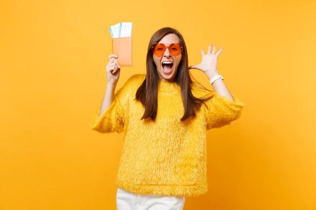 주황색 하트 안경을 쓴 흥분한 젊은 여성이 손을 벌리고 비명을 지르며 노란색 배경에 격리된 여권 탑승권을 들고 있습니다. 사람들은 진실한 감정, 라이프 스타일. 광고 영역입니다.