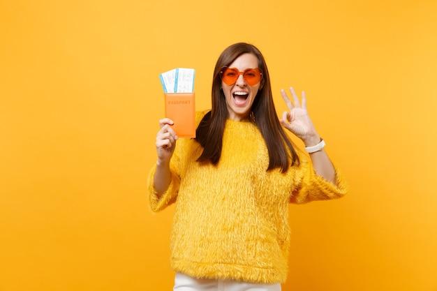 밝은 노란색 배경에 격리된 여권과 탑승권을 들고 있는 확인 표시를 보여주는 주황색 하트 안경을 쓴 흥분한 젊은 여성. 사람들은 진실한 감정, 라이프 스타일. 광고 영역입니다.